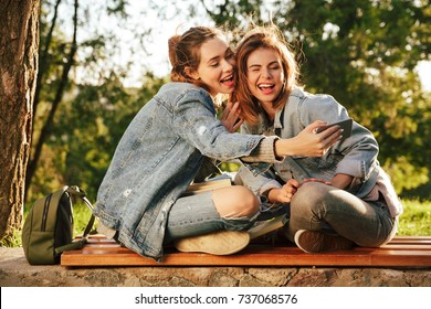 Two cheerful young woman showing taking selfe on smartphone while sitting on wooden bench in sunny park