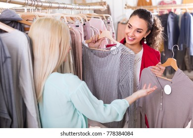Two cheerful young women choosing jersey at the apparel store