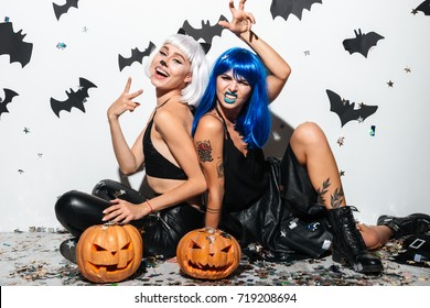 Two cheerful young women in leather halloween costumes posing with curved pumpkins over bats and confetti background
