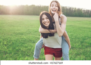 Two cheerful young women on the nature under sunlight