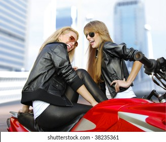 two cheery beautiful blonde motorcyclists and red motorcycle