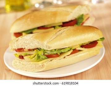 TWO CHEESE SALAD BAGUETTES ON PLATE
