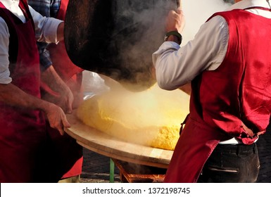 Two chef  pour the just made and still steaming  Polenta onto the traditional round wooden cutting board.