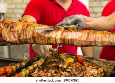 Two chefs carving a spit roast over a barbecue fire using a sharp kitchen knife to slice of thin slices for a buffet or takeaway menu