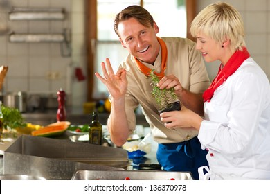 Two chefs in teamwork - man and woman - in a restaurant or hotel kitchen cooking delicious food