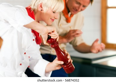 Two chefs in teamwork - man and woman - in a restaurant or hotel kitchen cooking delicious food, she is using a pepper mill (FOCUS ON MILL!)