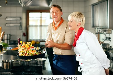 Two chefs in teamwork - man and woman - in a restaurant or hotel kitchen cooking delicious food, he is working on the ratatoulle in the pan