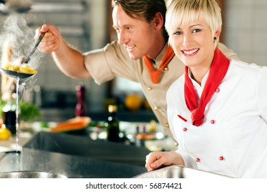 Two chefs in teamwork - man and woman - in a restaurant or hotel kitchen cooking delicious food, he is taking out the pasta