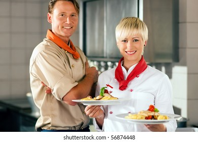Two chefs in teamwork - man and woman - in a restaurant or hotel kitchen cooking delicious food, both are presenting the finished dishes