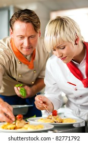 Two chefs in teamwork - man and woman - in a restaurant or hotel kitchen cooking delicious food, both are decorating the dishes