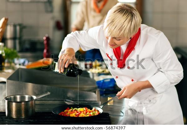 Deux chefs en équipe - homme et femme - dans un restaurant ou une cuisine d'hôtel cuisinant une cuisine délicieuse, elle met de l'huile d'olive dans la ratatatouille