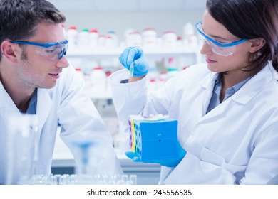 Two chemists wearing safety glasses and working together in the laboratory