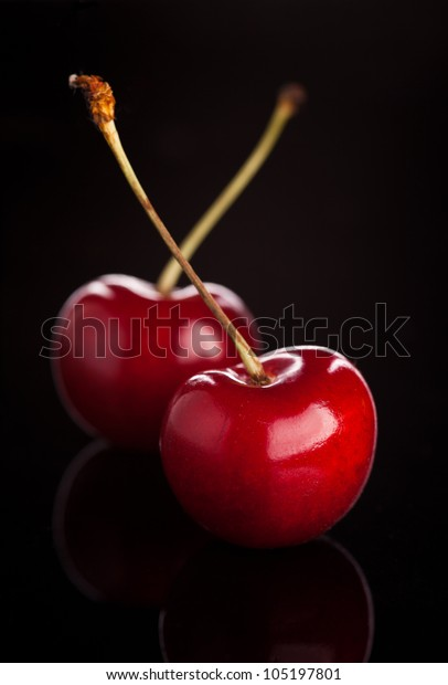 two cherries on black background