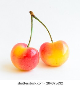 Two cherries on isolated white background. These cherries are grown in Yakima Valley, a prime agricultural area of Washington State and the largest variety of crops in the Pacific Northwest, USA.