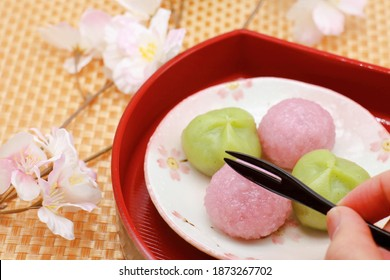 Two cherry blossom rice cakes and two grass rice cakes are on a plate with a cherry blossom pattern. Traditional Japanese sweets. Pink and green rice cakes. A classic springtime food.