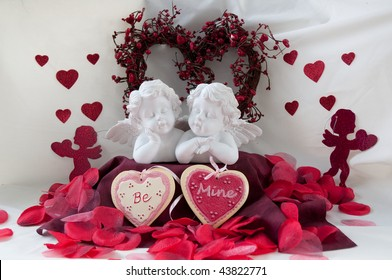 two cherubs with a heart shaped wreath and hearts that say BE MINE with rose petals.