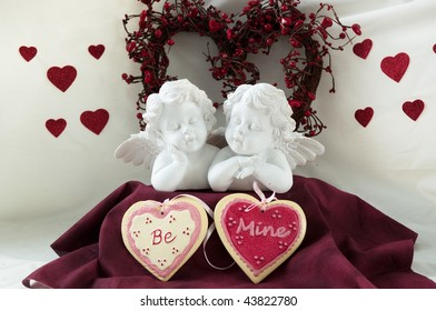 two cherubs with a heart shaped wreath and hearts that say BE MINE