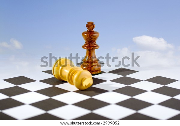 Two chess kings on board, one standing, one fallen, blue sky, white clouds background. Looks like  flying carpet. Concepts of winning, last man standing, best man wins. Focus on standing king.