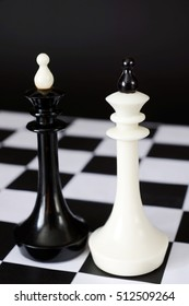 Two chess kings one in front of other. Fight of equal competitors. Concept with chess pieces against black background