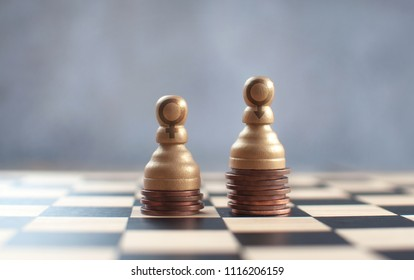 Two chess pawns with gender symbols on top of a heap of coins