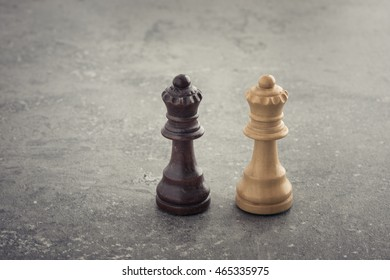 Two chess queens side by side on stone table with copy space. Concept of strategy, competition and female rivalry.