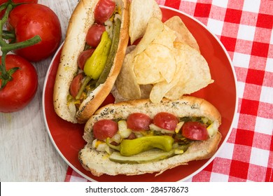 Two Chicago style hot dogs on a red plate with potato chips and tomatoes