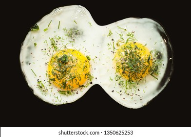 Two chicken eggs fried in a scrambled egg with raw yolks and greens on a dark background, isolate