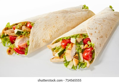 Two chicken and salad wraps on studio background