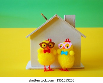 Two chickens in front of a piggybank and coin
