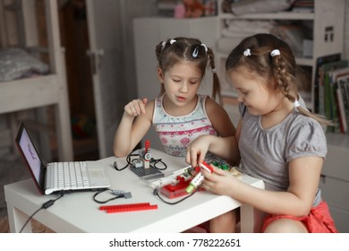 two child girls are assembled by the designer at home, robotics, concept childhood and family activities