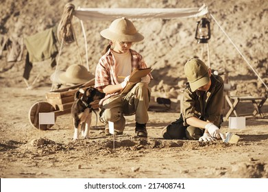 Two children archaeologists camped and conduct excavations of ancient tombs on a summer day