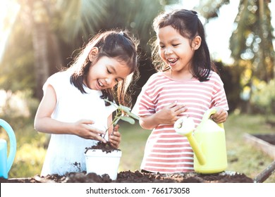Two children asian little girl having fun to plant seedling young tree in the pot together in vintage color tone