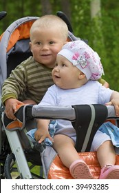 Two children in baby carriage. There is one year's difference of age between them. They are brother and sister