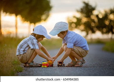 Two children, boy brothers, having fun outdoors with toy cars on sunset