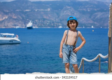 Two children, boy brothers, walking on a path around Mediterranean sea on French riviera, enjoying sunny summer afternoon