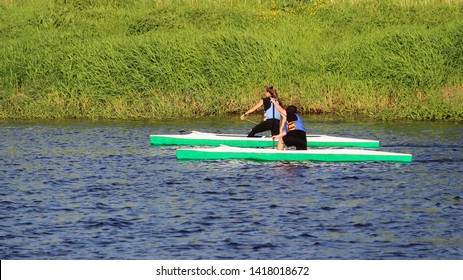 Two children boy and girl floats on kayak on the background of green shore - kid's sport training on the water, side view