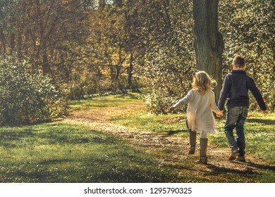 Two children, a boy and a girl holding hands and playfully walking along a hidden path in the woods towards the sunlight.