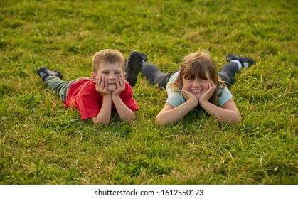 Two children, a boy and a girl, lying on grass smiling.