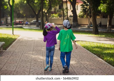 Two children a boy and a girl walking in the park on a sunny summer day.