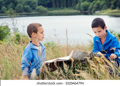 Two children boy reading a map while on a hike in nature.