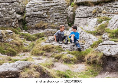 Two children boys, friends or brothers sitting on ground on a rock talking, Dartmoor, England, UK.