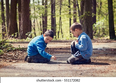 Two children boys playing in forest park, drawing with chalk on the ground.