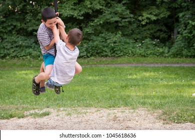 Two children boys playing together on a zip line swing in the park in summer.