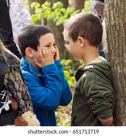 Two children boys talking and playing  together among other people during a summer camp or adventure event in the forest in the nature.