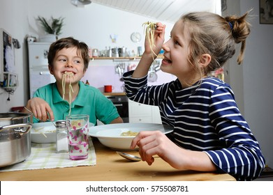 Two children, brother and sister, are being silly while eating spaghetti at home in their kitchen