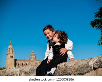 Two children brothers embraced on the Roman bridge of Salamanca, dressed in traditional clothes and Salamanca cathedral