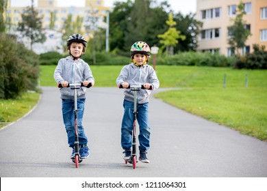 Two children, brothres, riding scooters in the park on a sunny autumn day, family activities during weekends