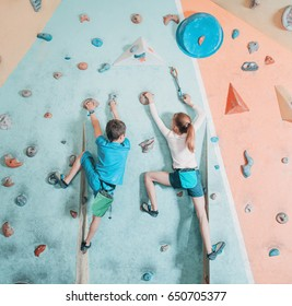 Two children climbing on artificial boulder practical wall in gym.