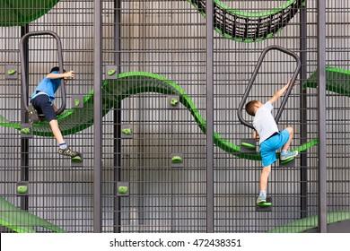 Two children climbing on a metal frame of modern children playground.