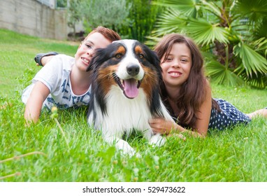 Two children and a dog outdoors